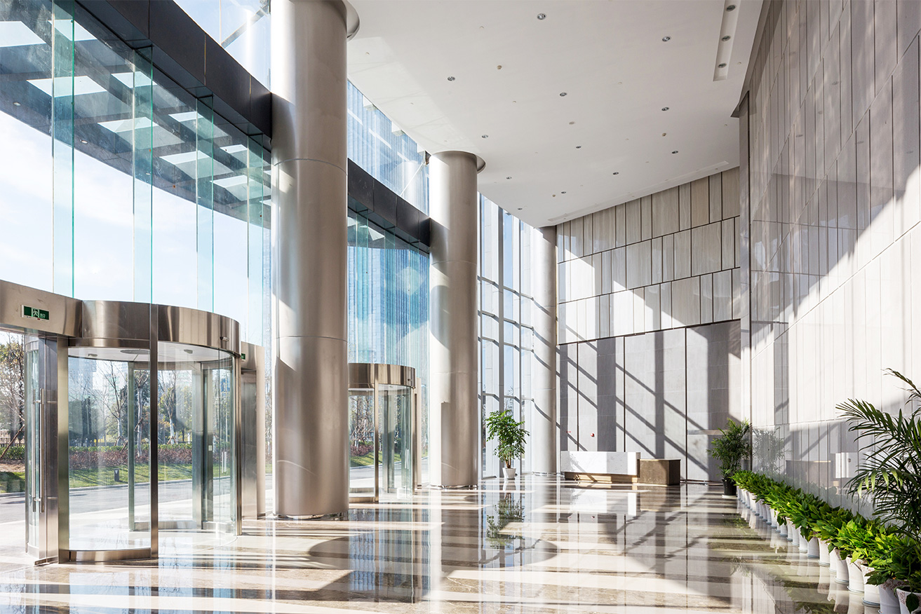 Modern office building entrance hall with glass front and plants