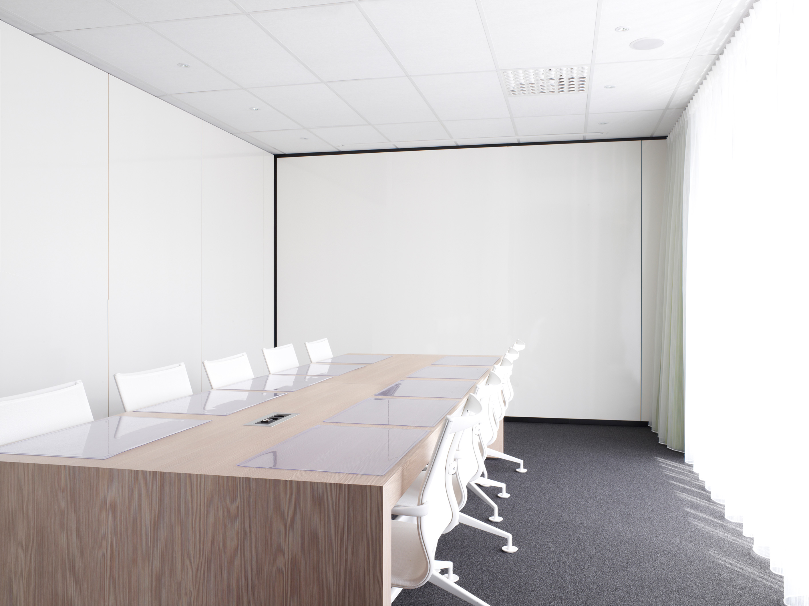 modern meeting room with white chairs and wooden conference table